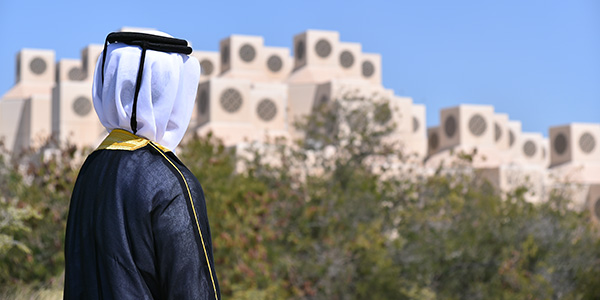 photo of an alumni student with qatar university in the background