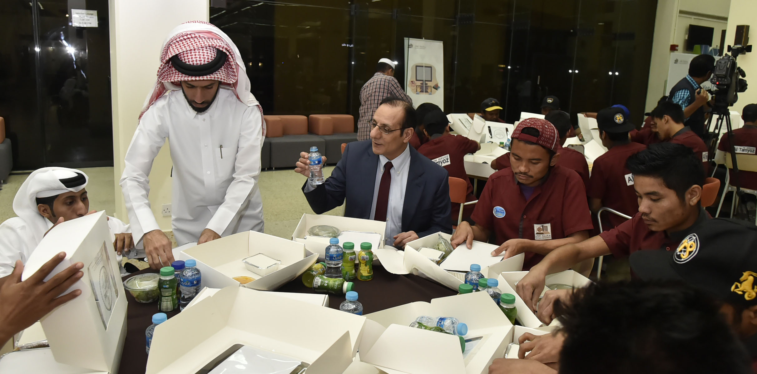 Photo of special needs students and special needs center staff eating Iftar with cleaners in Qatar University